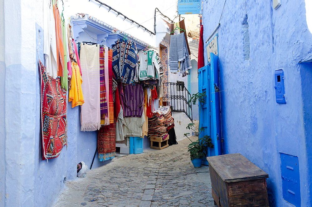 Displayed carpets and rugs in Chefchaouen's medina, Morocco.