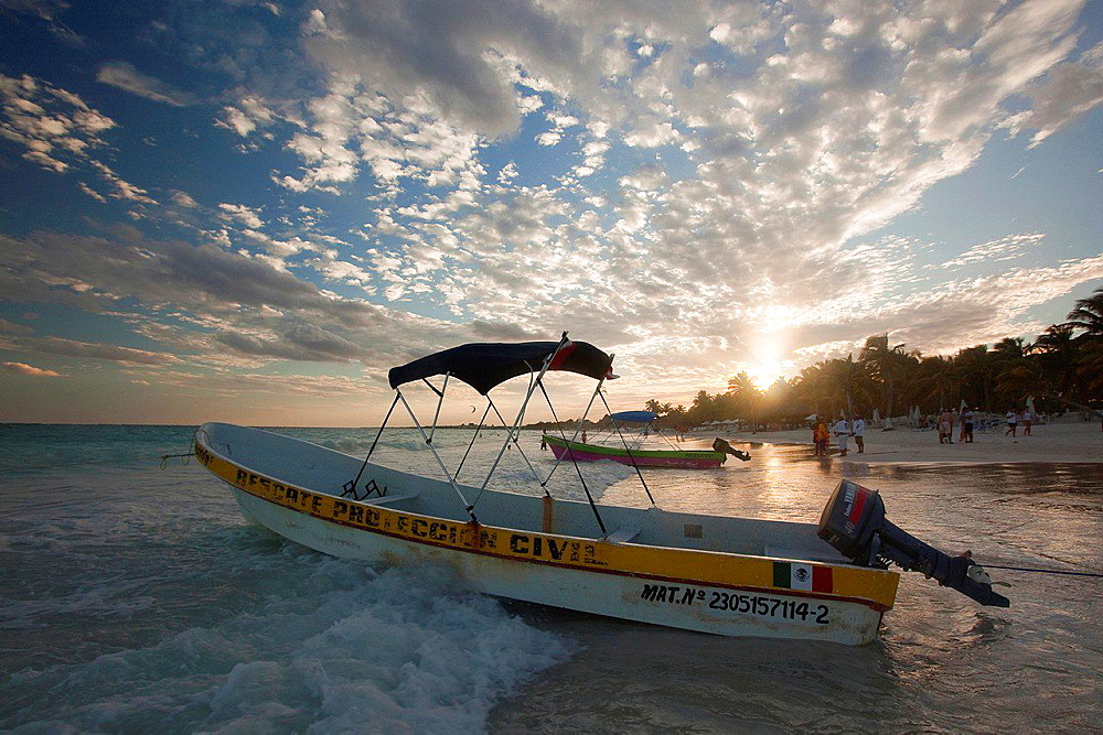 Fishing boats at sunset on Tulum public beach, Tulum, Quintana Roo, Yucatan Province, Mexico.