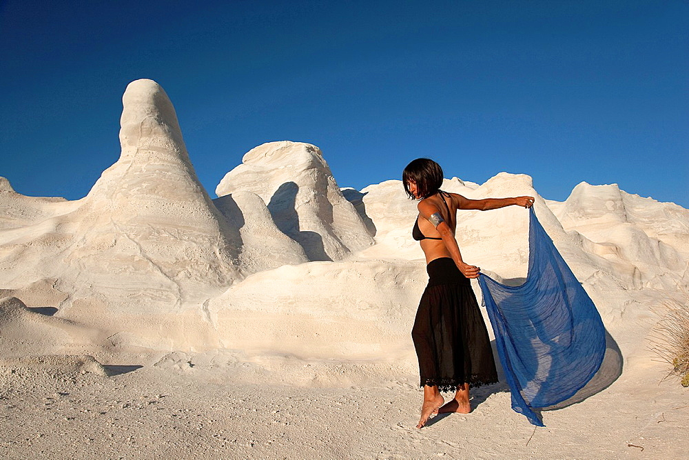 Woman posing near the white rock forms in Sarakiniko beach, Milos, Cyclades Islands, Greek Islands, Greece, Europe.