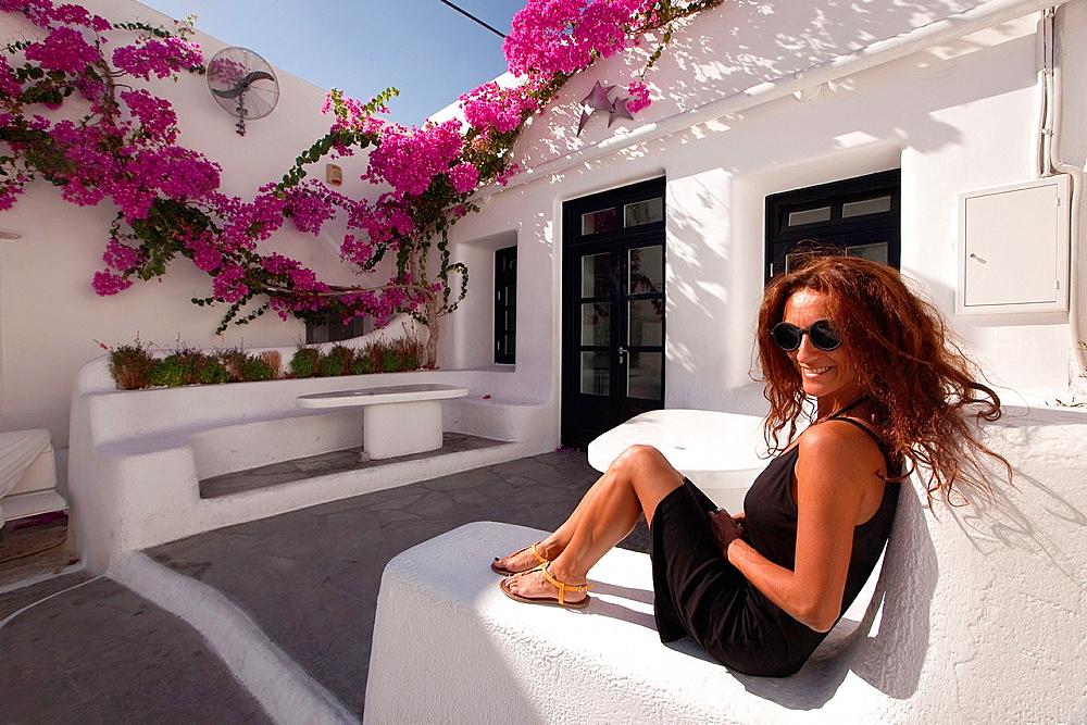Woman sitting in a cafe, Mykonos, Cyclades Islands, Greek Islands, Greece, Europe.