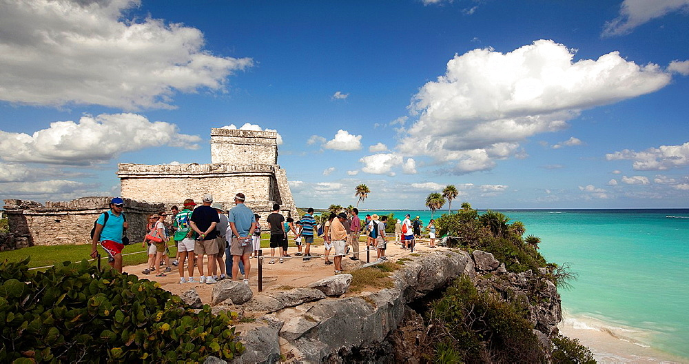 El Castillo and the rocky beach with the visitors at Mayan Ruins, Tulum, Quintana Roo, Yucatan Peninsula, Mexico.