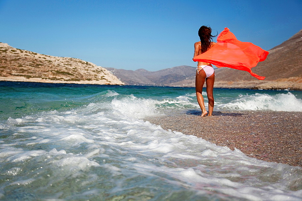 Woman in bikini walking towards the waves at the beach, Amorgos, Cyclades Islands, Greek Islands, Greece, Europe.