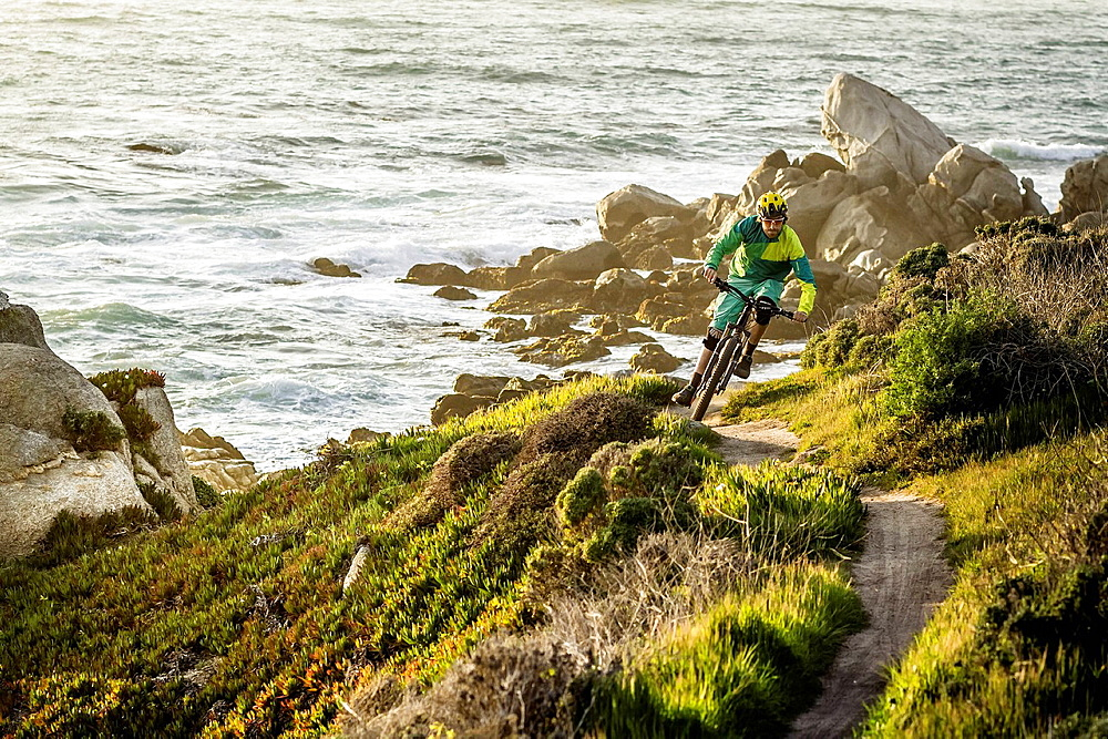 Mountain biker riding up coastal path, Monterey Bay area, California, USA