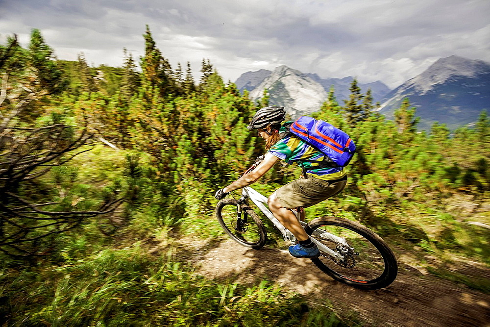 Mountain biker cycling on dirt track in mountains