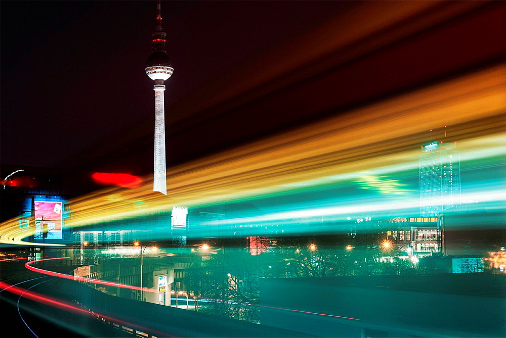 Night time view of moving train and television tower, Berlin, Germany