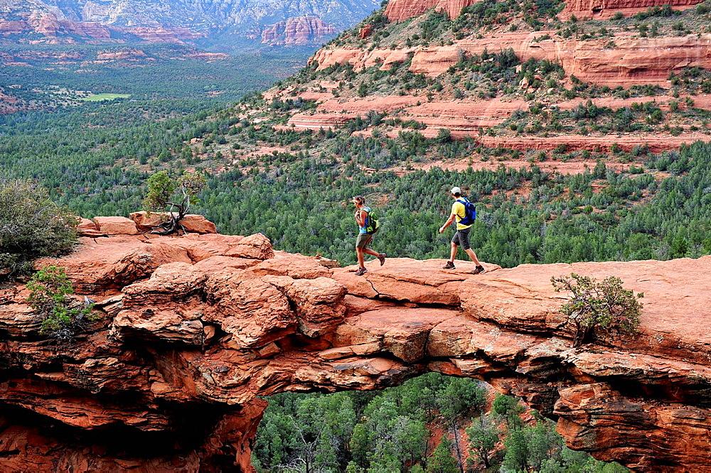 Hiking couple on arched rock formation, Sedona, Arizona, USA