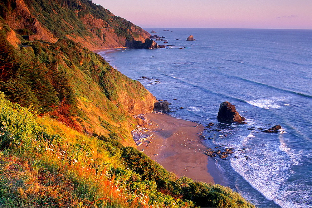 Sunset light on coastal cliffs over beach near Crescent City, California.