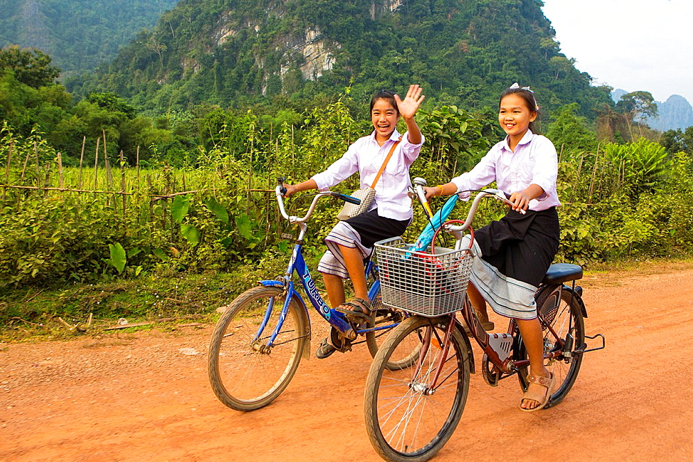 Children returning home after school on thier bicycles, Vang Vieng, Laos.