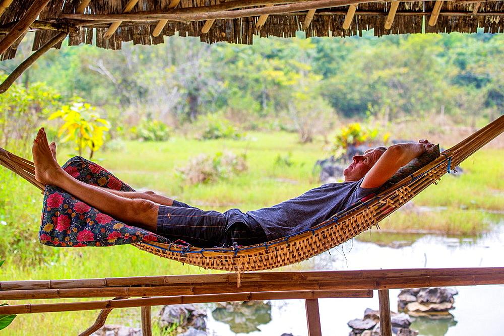 Tourist relaxes in a bamboo hammock, Vang Vieng, Laos.