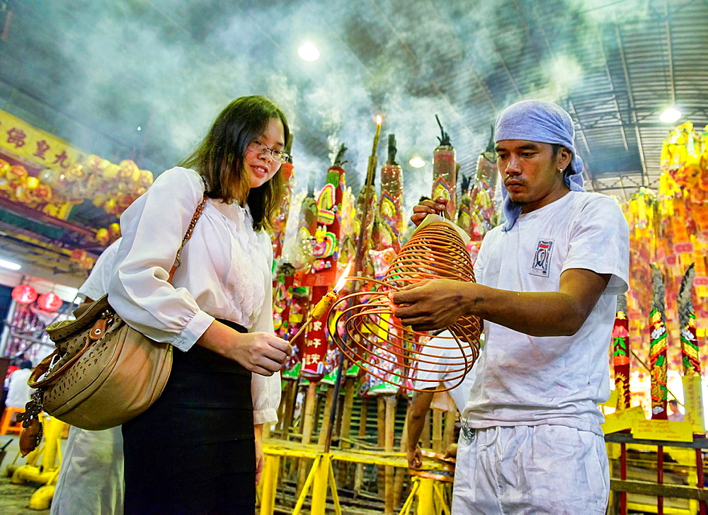 lighting candles for good luck at the Vegetarian Festival in Bangkok, Thailand. - 817-465716