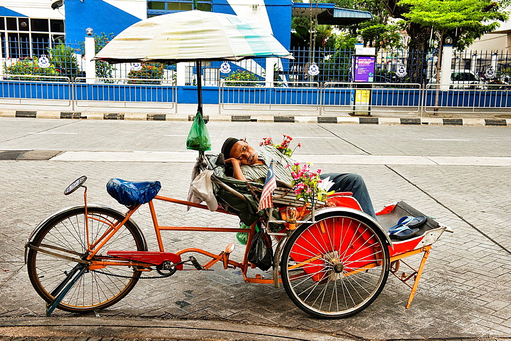 sleeping in a becak (trishaw) in Georgetown in Penang, Malaysia.