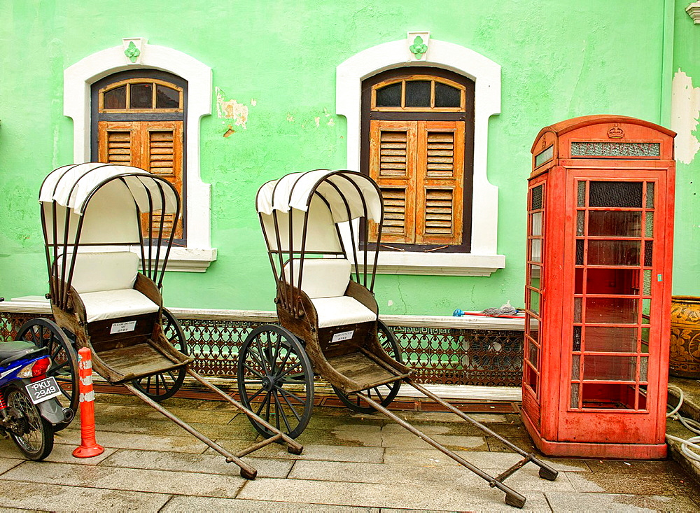 trishaws and phone booth at the Pinang Peranakan Mansion in Georgetown, Penang, Malaysia.