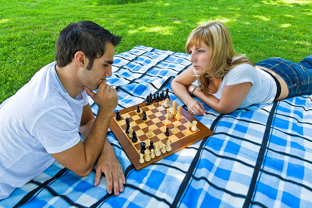 Young couple playing ches in the garden, Germany, Europe