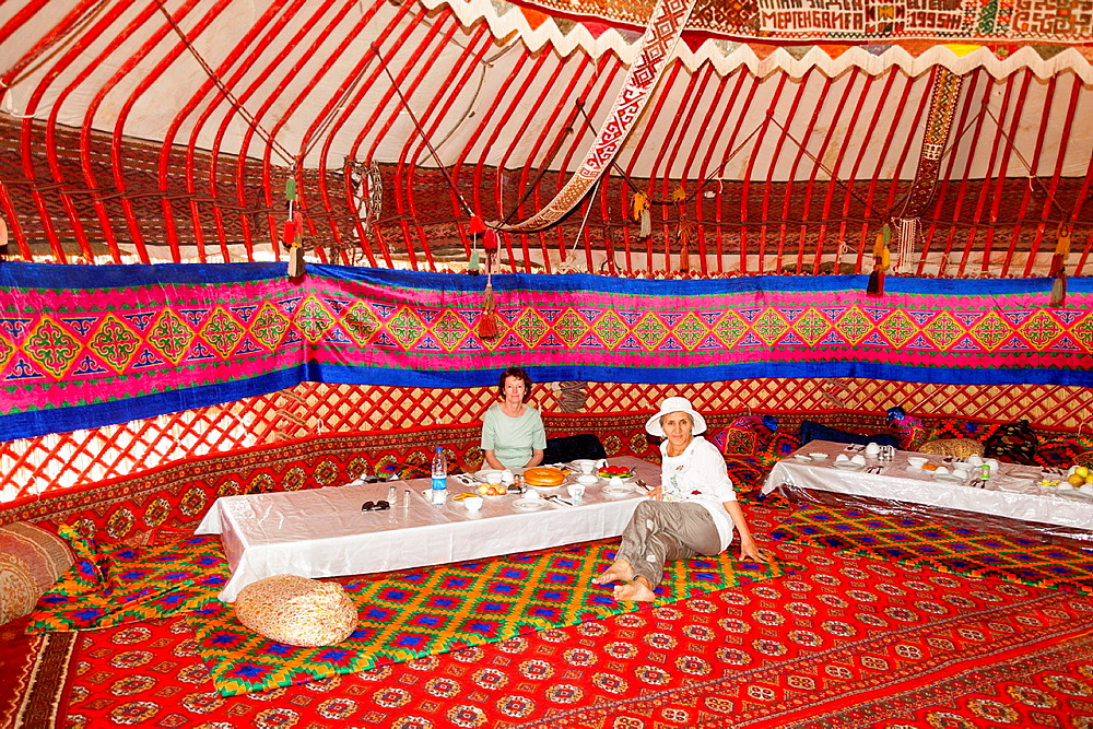 Tourists dining in a yurt, Ayaz Kala Yurt Camp, Ayaz Kala, Khorezm, Uzbekistan.