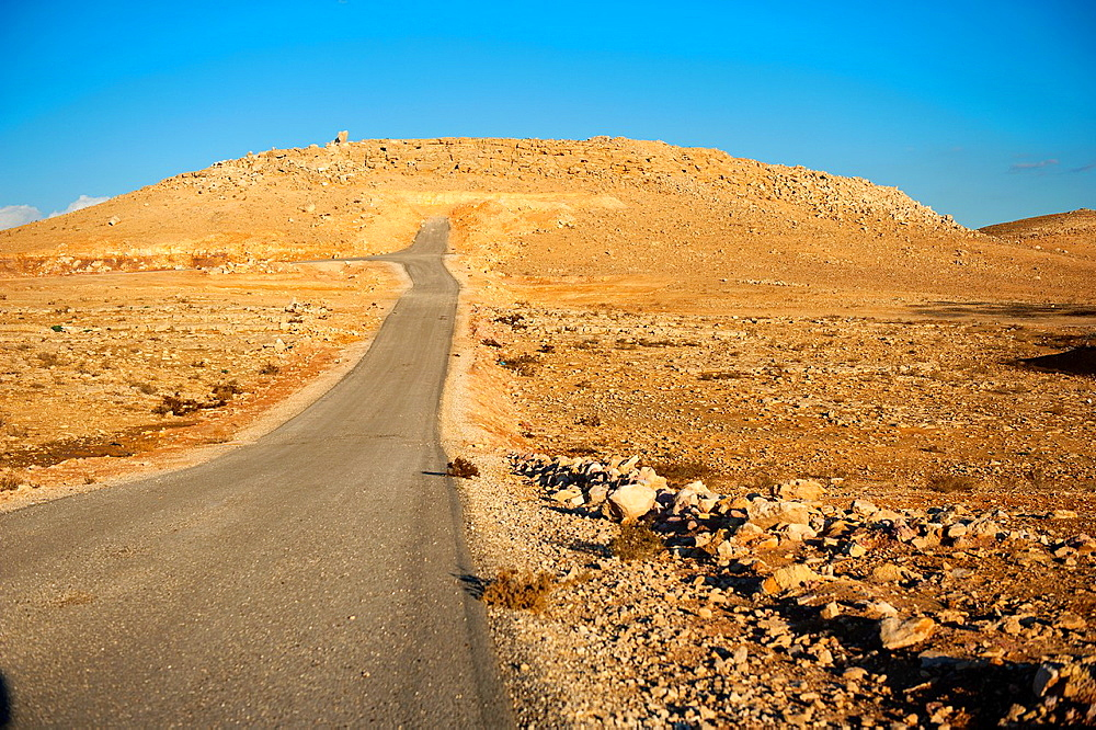Al Thughra, Al Mafraq, Jordan, Middle-East. Most of the Jordanian landscape exists of a dry dessert with rocks and stones, with incidental roads leading nowhere.