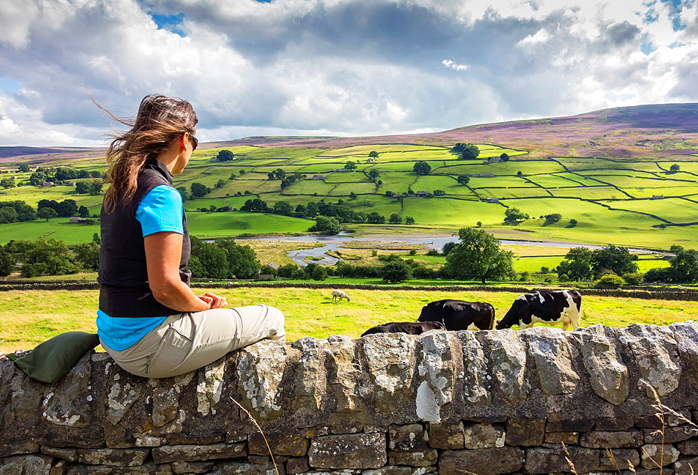 Female hiker sitting on wall near Reeth village in The Yorkshire Dales National Park, England, United Kingdom.