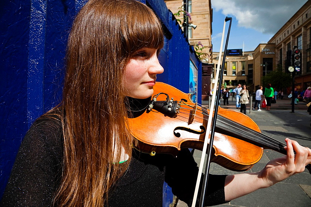 Young woman busking in Buchanan Street, Glasgow, Scotland