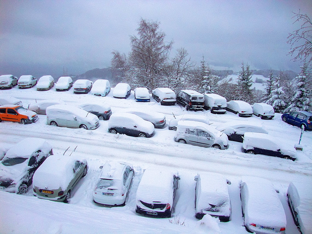 with snow covered cars at parking place in Prapoutel, France