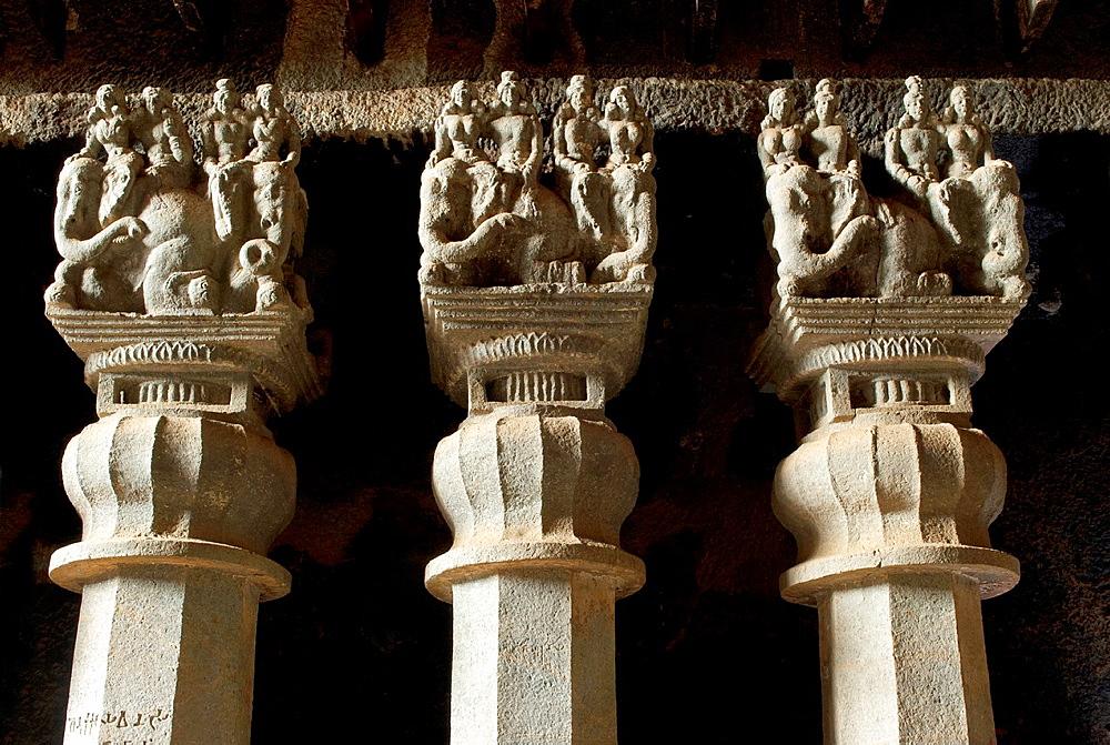 Three pillars- octagonal shaft, inverted bell capital and couples riding elephants. Circa 2nd. Century CE Karla Caves, dist Pune, Maharashtra, India