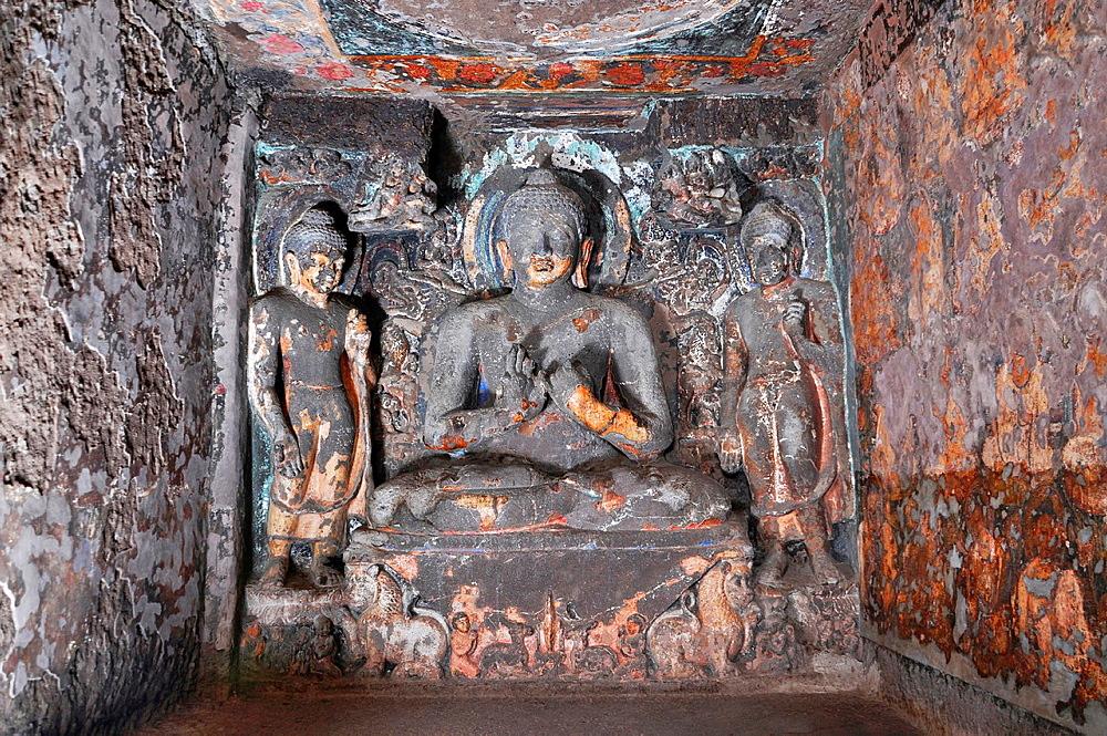 Cave 6 Upper: Right front shrinelet. Buddha image with two Bodhisattva's on either side. Ajanta Caves, Aurangabad, India.