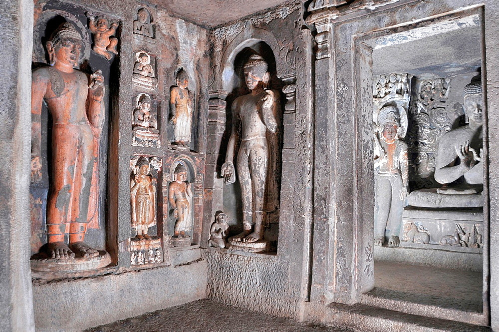 Cave 6 Upper: Buddha image, left flywhisk bearer, and intrusive Buddha images. Ajanta Caves, Aurangabad, Maharashtra, India.