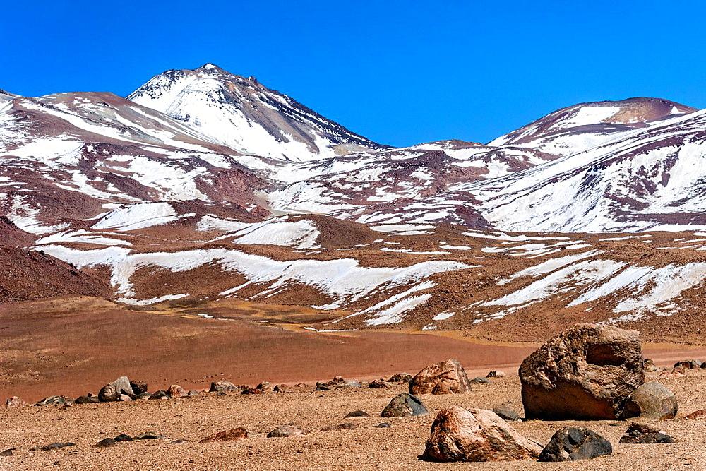 Landscape of glacier-moved rocks at base of snow-capped mountains and Licancandur volcano, near Bolivian and Chilean border, Reserva de Fauna Andina Eduardo Avarda, Bolivia, South America.