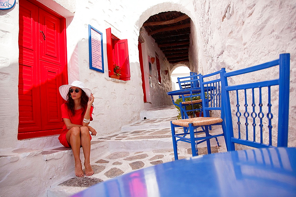 Woman in red sitting barefoot at the side of the street, Amorgos, Cyclades Islands, Greek Islands, Greece, Europe.