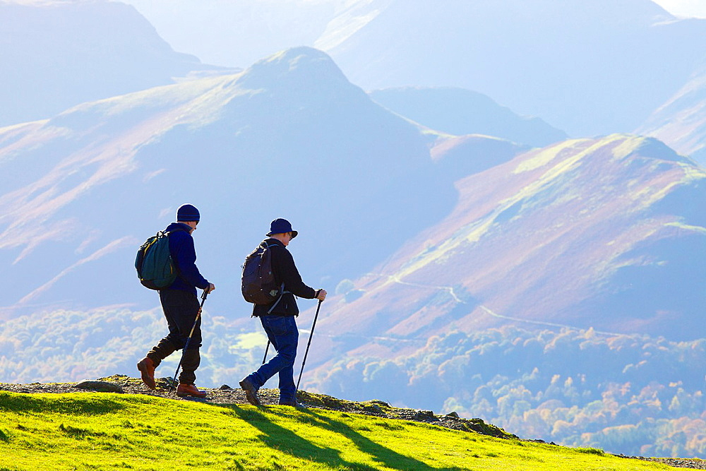 Hikers walking on Latrigg with Cat Bells behind Lake District National Park Cumbria England United Kingdom Great Britain. - 817-472191