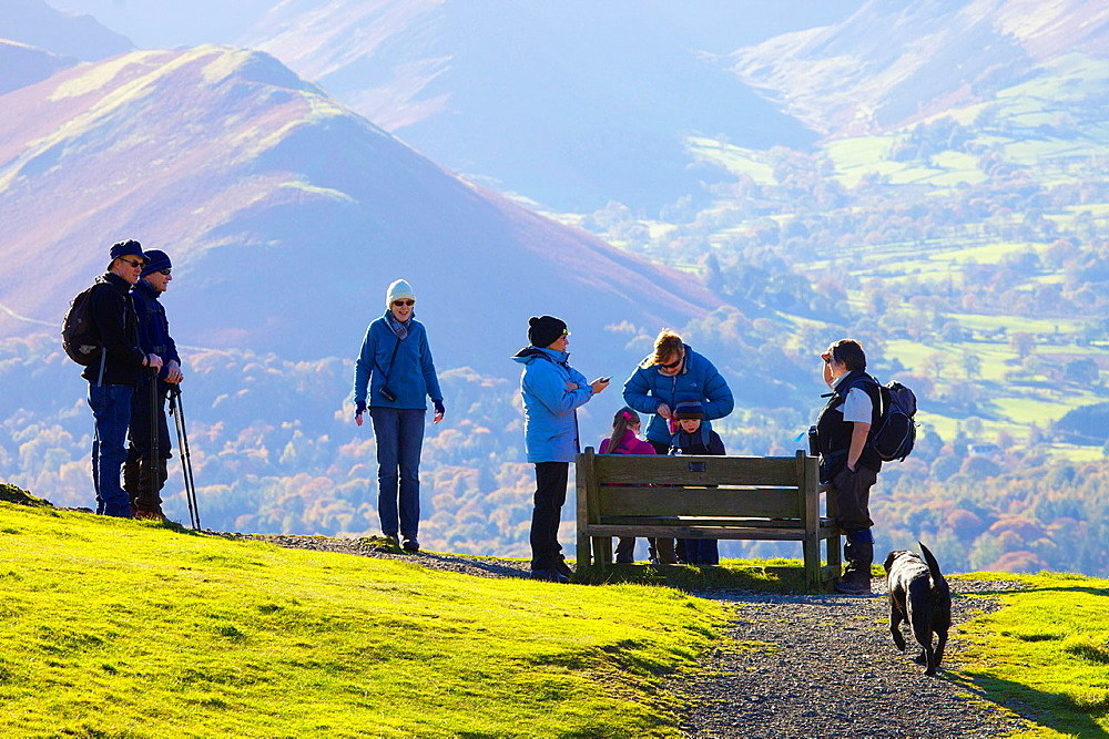 Tourists standing near and sitting on a bench, enjoying the view from Latrigg Lake District National Park Cumbria England United Kingdom Great Britain. - 817-472192