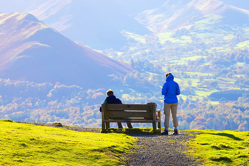 Tourists standing and sitting on a bench, enjoying the view of Cat Bells in the Lake District National Park Cumbria England United Kingdom Great Britain. - 817-472193