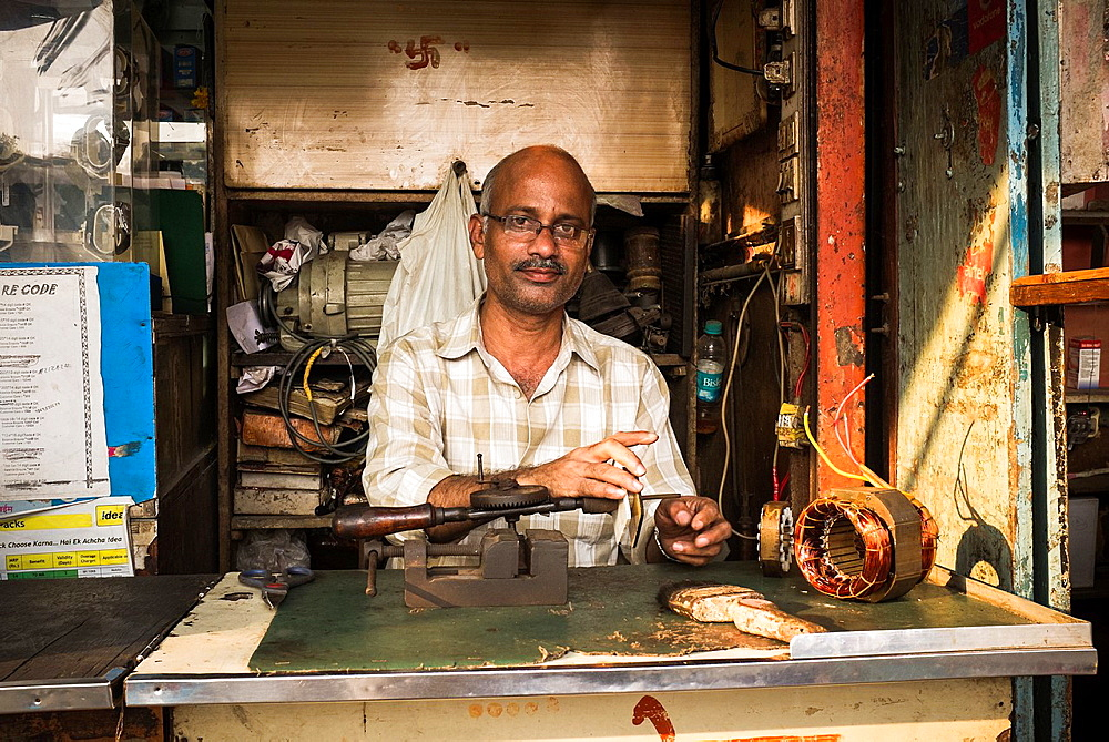 A man sits behind the counter in his shop repairing small electrical equipment. - 817-472294