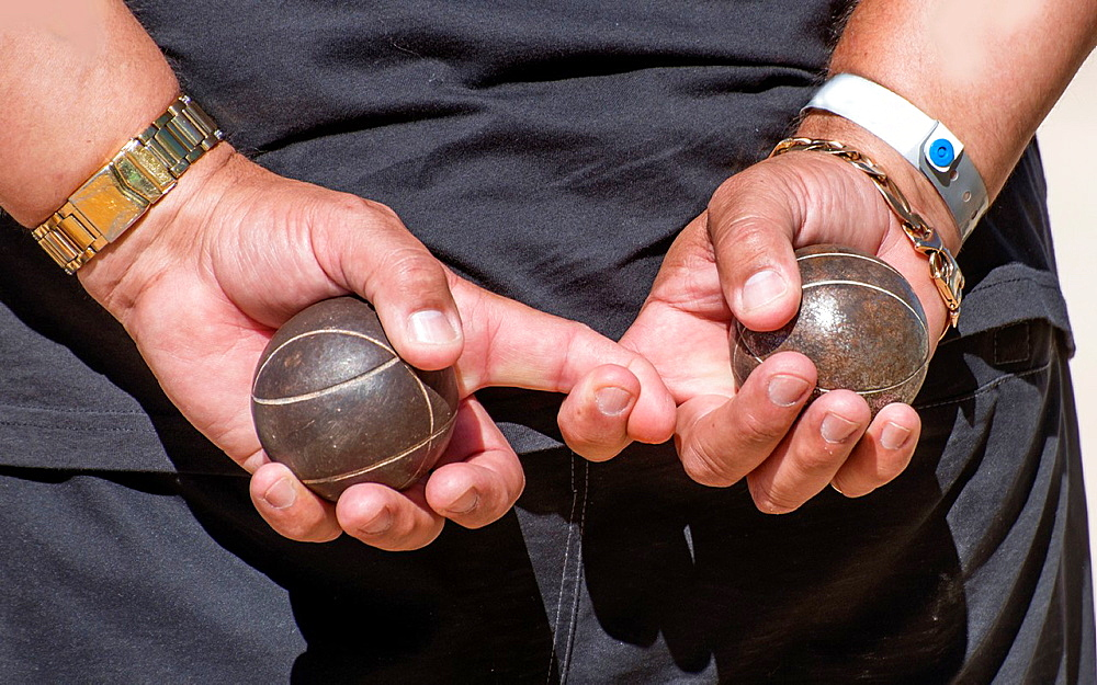 Two metal balls for game in petanque in man's hands. - 817-472312