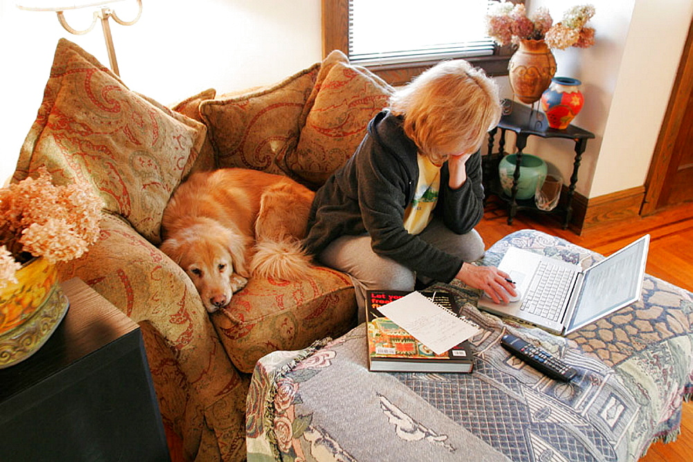 Woman working on laptop with golden retriever dog on couch