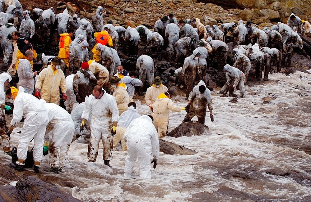 Volunteers dressed with protective clothing gathering the fuel spill ('chapapote') of Prestige tanker, Dec, 2002, Galicia, Spain - 817-65200