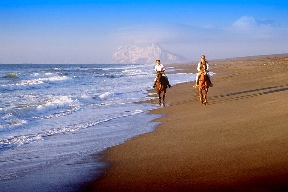 Horse riding at Sotogrande beach with the Rock of Gibraltar in background, Cadiz province, Spain