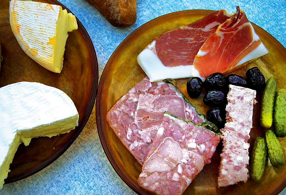 Food: Reblochon and Camembert cheeses, Pate de Tete and Pate de Campagne, ham, black olives and 'Cornichons', Dordogne, France.