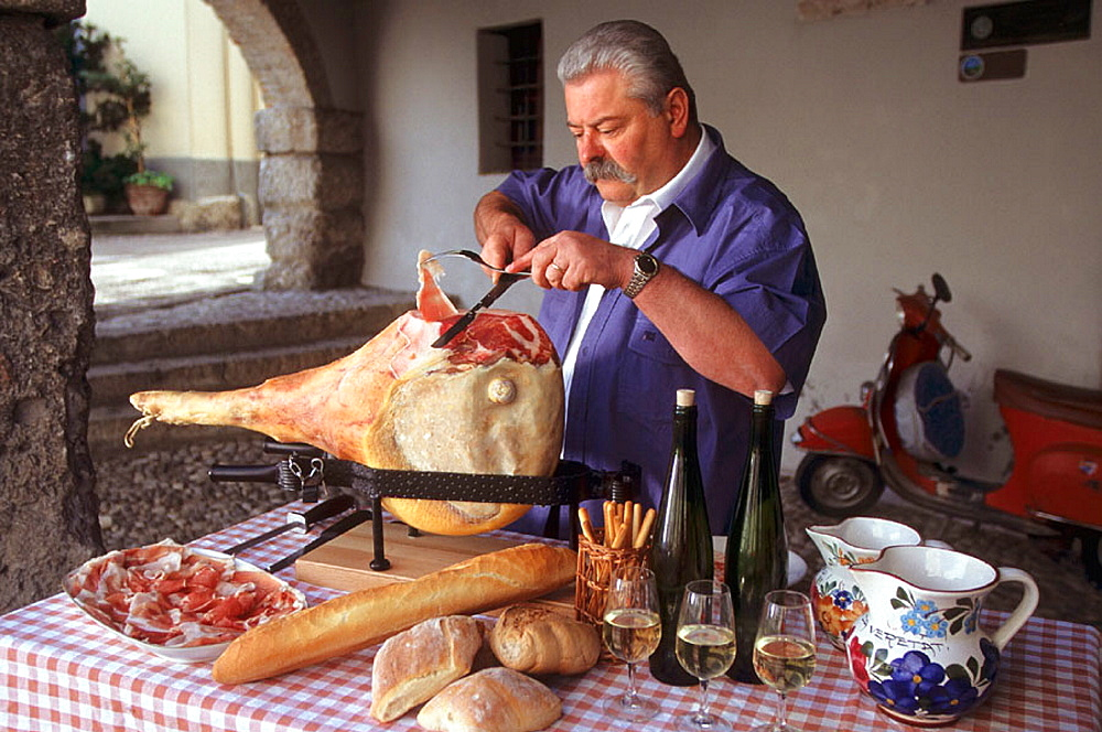 San Daniele ham is usually served sliced tissue-paper thin, wrapped around grissini (breadsticks); grissini are pencil-sized sticks of crispy, dry bread, San Daniele ham, Friuli, Italy.