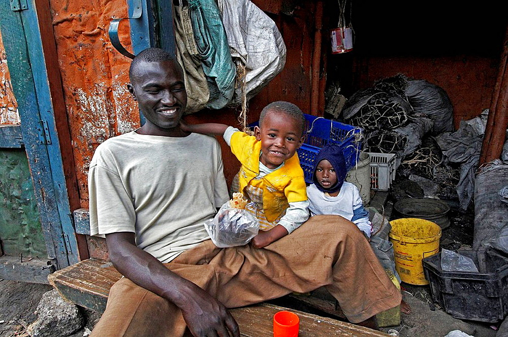 Man and his children, charcoal sellers, Mukuru Ruben, a slum of Nairobi, Kenya