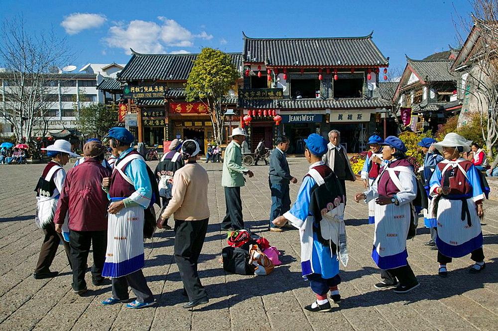 China, Yunnan Province, Lijiang, Lijiang Old Town, Women in Naxi Minority clothes dancing on Dong Dajie Street, the Naxi People are the main ethnic group in Lijiang