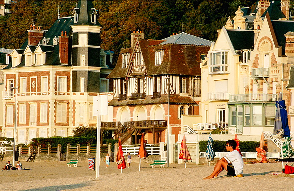 France, Normandy, Bathing Station, Deauville-Trouville, Parasols, path called 'les Planches' kind having a rest by the beach