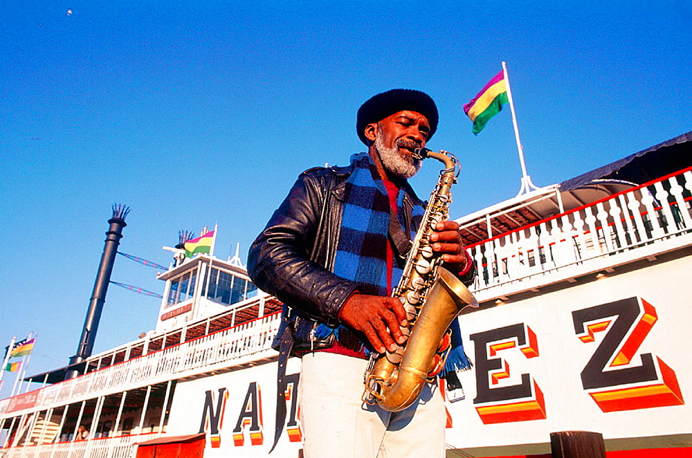 Musician playing in front of steamboat 'Natchez' on Mississippi river, New Orleans, Louisiana, USA