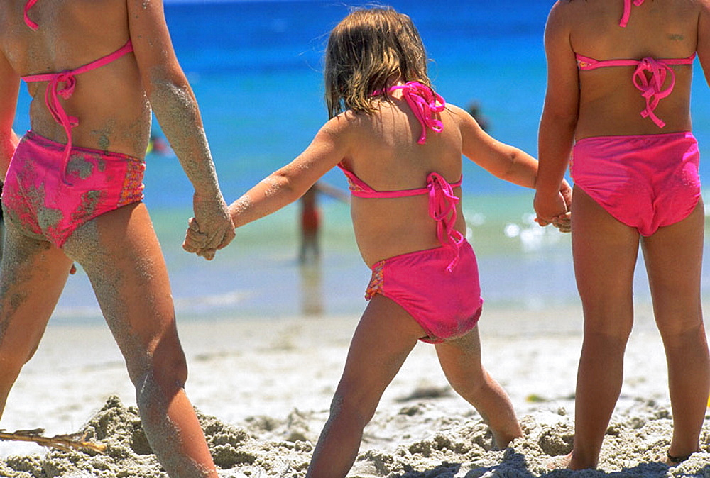 Three sisters holding hands at the beach