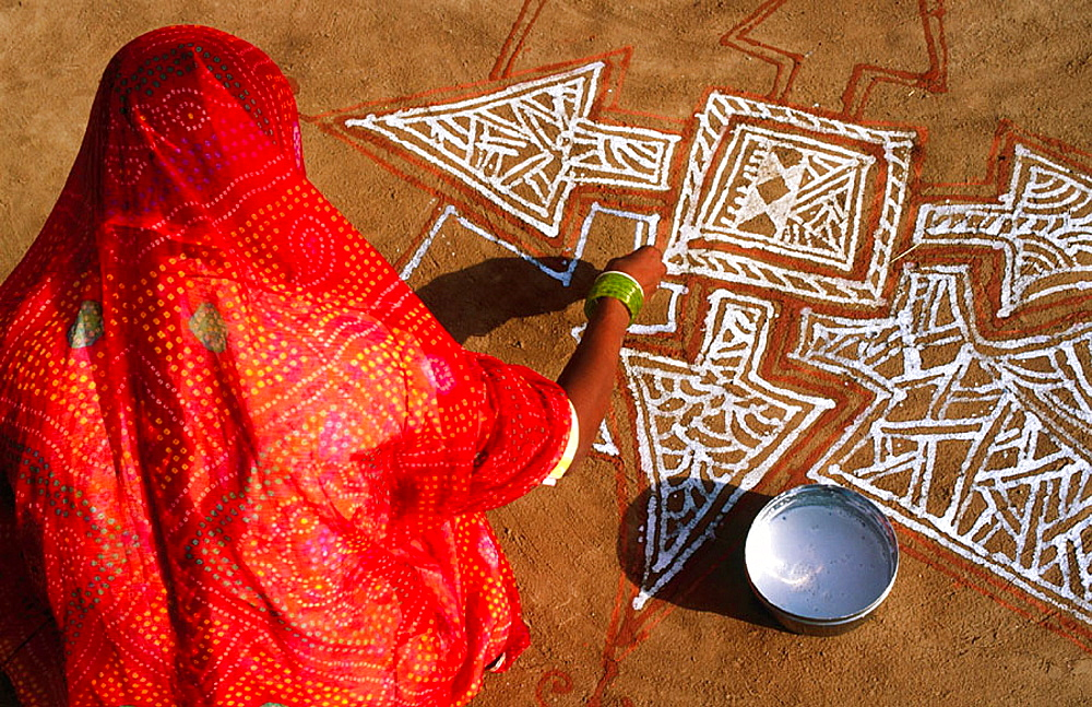 Indian woman painting a mandana (colourful floor design) in Rajasthan, India