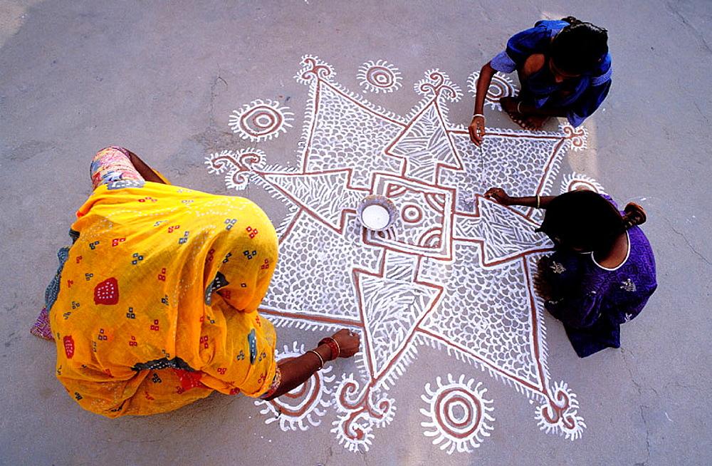 Three women painting a mandana (colourful floor design), village near Tonk, Rajasthan, India