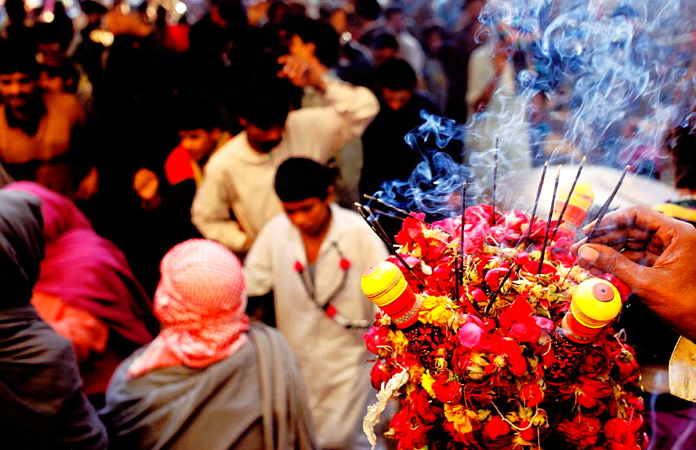 Man with incense sticks during ceremony at the tomb of Sufi saint Lal Shabaz Qalandar, Sehwan Sharif, Sindh province, Pakistan