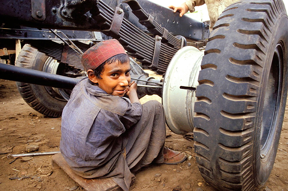 Garage mechanic, Young boy at work, Peshawar, NWFP (North-West Frontier Province (northwest Pakistan), Pakistan.