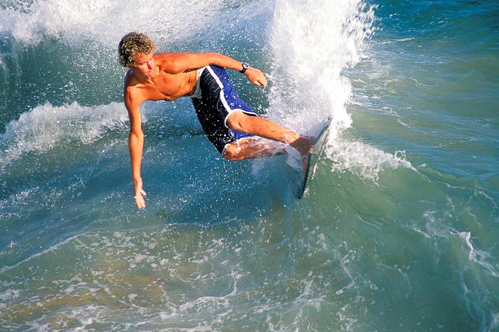 Surfer surfing on breaking wave using a skimboard, near Balboa Pier, Balboa Island, Newport Beach, California