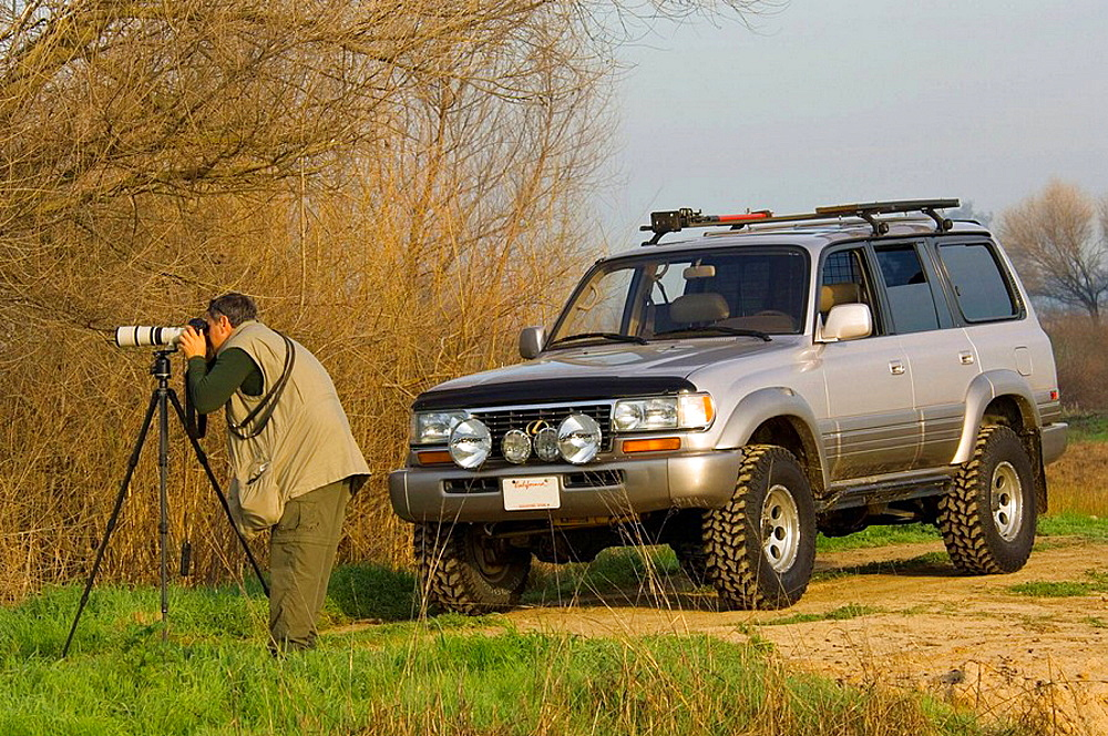 Photographer photographing riparian habitats next to SUV in the Merced National Wildlife Refuge, Central Valley, California, USA