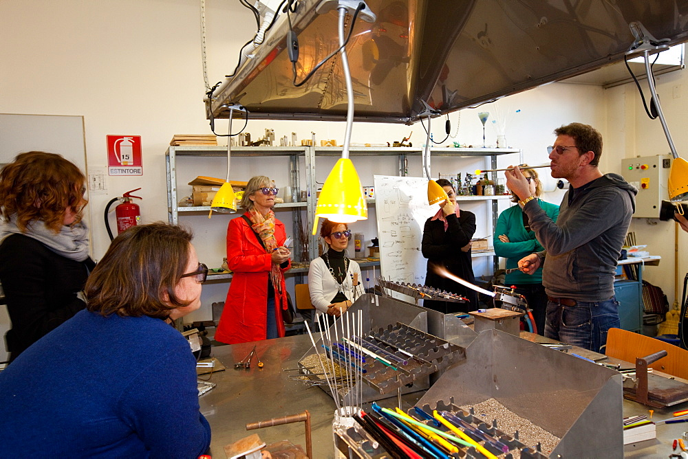 Muranese instructor teaching to a group of students the lampworking technique to make glass beads, Abate Zanetti glass school, Murano island, Venice, Veneto, Italy, Europe