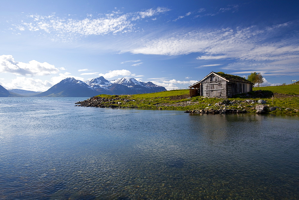 Cabin with traditional grass roof overlooking a fjord and snowy mountains in Lyngen Peninsula, Troms county, Norway, Scandinavia, Europe